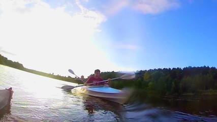 Travelers kayaking at sunset, action camera, underwater, slow-mo