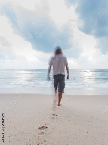 Back view of a man walking on the sand of a beach © Netfalls