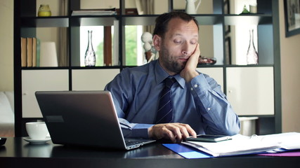 Young, bored businessman sitting by desk at home