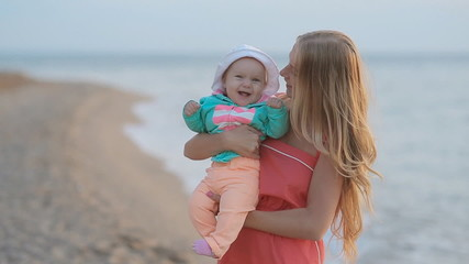 Young mother holding baby in her arms while standing near the
