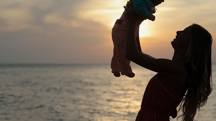 Silhouette of mother kissing baby at sunset near the sea