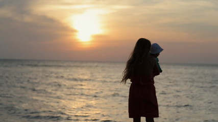 Silhouette of mother holding baby while standing near sea at