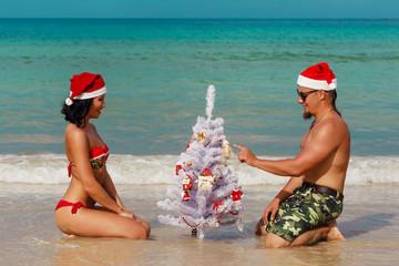 sexy girl man Santa on a beach fir-tree
