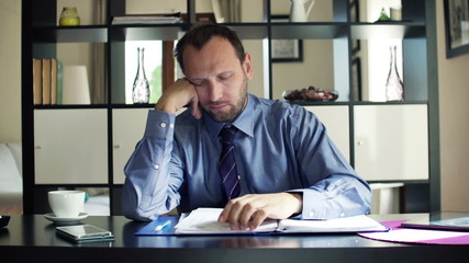 Tired businessman yawning and sleeping sitting by desk at home