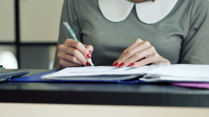 Businesswoman hands making notes in documents sitting by desk