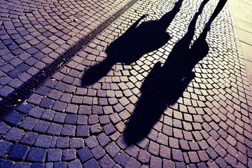 People walking, casting shadows on cobblestones