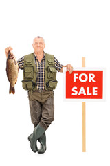 Smiling mature fisherman holding a fish next to a panel noted