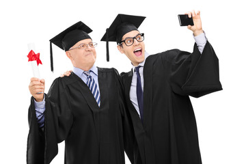 Senior and guy in graduation gowns taking a selfie