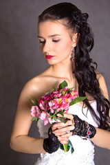 Portrait of a young beautiful fiancee with a bunch of pink flowe