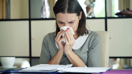 Sick young businesswoman blowing her nose in paper tissue