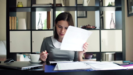 Young, beautiful businesswoman signing documents sitting by desk