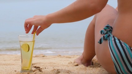 Torso of Sexy Woman with Fresh Drink on Beach. Back View.