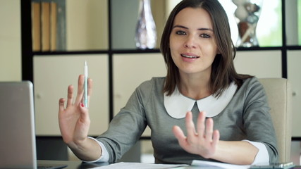 Happy businesswoman telling good news to camera sitting by desk