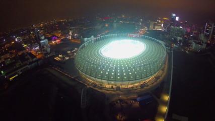 Aerial of large illuminated stadium at night, city landmark