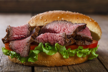 roast beef hamburger sandwich on a wooden surface