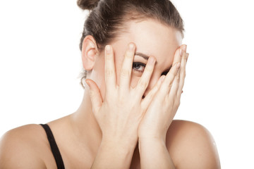 shy young woman covering the eyes and looking through fingers