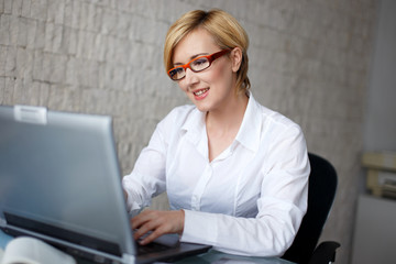 Blonde businesswoman in typing on laptop