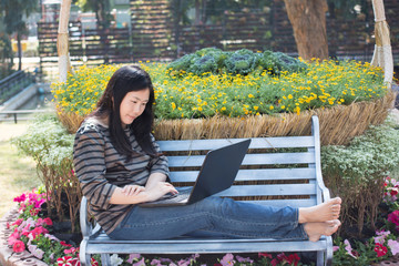 young woman using laptop in the autumn park