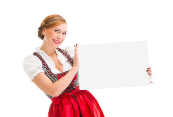 Bavarian woman in dirndl, holding blank signboard.