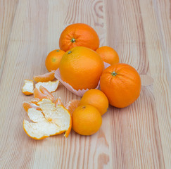 Oranges in paper small baskets on wooden texture with tangerines