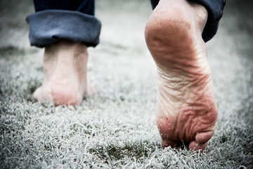 Barefoot walking on frosted grass