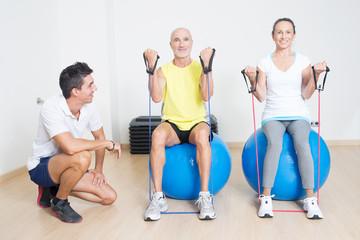 Zwei Senioren beim Seiltraining auf Fitnessball mit Trainer