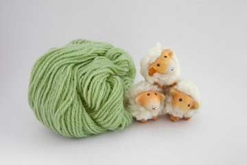 Cute sheep playing together with a ball of green wool