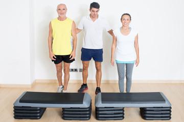 Trainer hilft Senioren beim step training