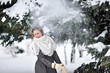 beautiful woman in winter knitted mittens throws snow