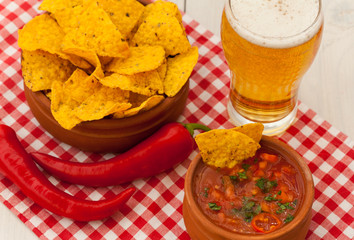 Salsa with tortilla chips, chilli peppers and glass of beer