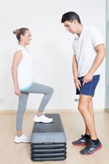 Trainer hilft Seniorin beim step training