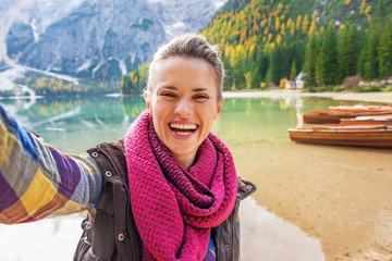 Happy young woman making selfie on lake braies in italy