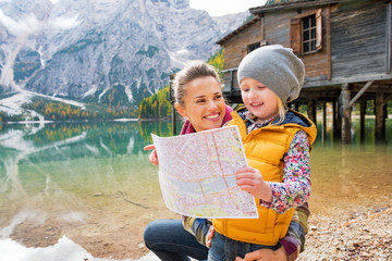 Portrait of mother and baby with map on lake braies in italy