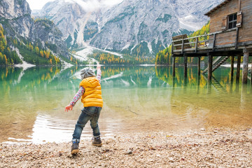 Child throwing stones on lake braies in south tyrol, italy