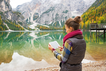 Young woman using tablet pc while on lake braies in south tyrol