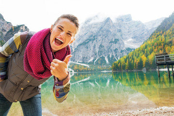 Happy young woman on lake braies in south tyrol, italy