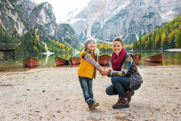Portrait of happy mother and baby on lake braies in south tyrol