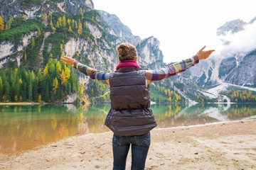 Young woman on lake braies in south tyrol, italy rejoicing
