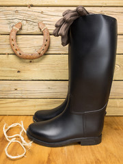 riding boots and gloves in a stable