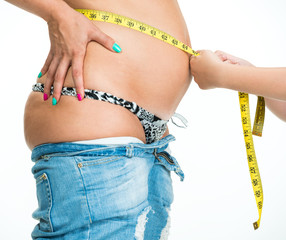 Daughter measuring mother's waistline  with centimeter