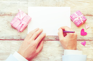 male hand writing a letter