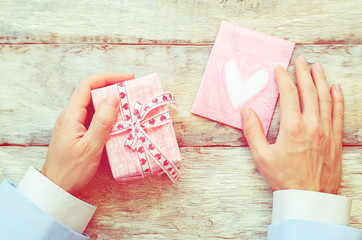 male hand holding card and gift
