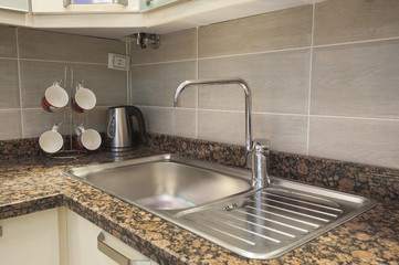 Sink and tap with kettle in apartment