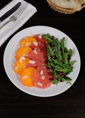 Salad of grapefruit, persimmon, pomegranate and rocket salad