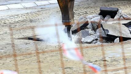 Jackhammer machine digging up concrete road