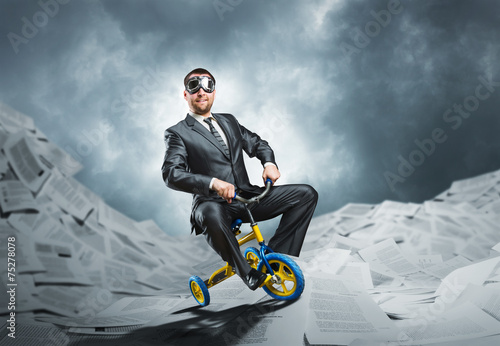 Odd businessman riding a small bicycle - 75278078