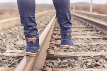 Feet on urban shoes on a train railway