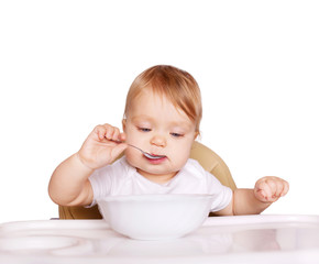 Baby eating healthy food. Isolated on white