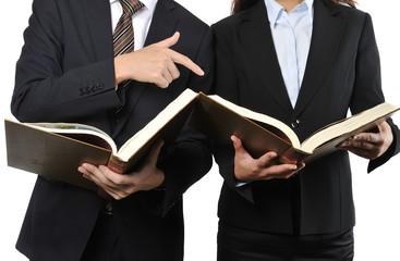 難しい本を読んで調べている男女の二人のビジネスマン