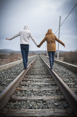 Young couple walking on a railway. Rural setting